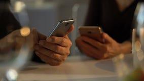 Взрослая пар скроллинга smartphones дата вместо романтичная в ресторане, игнорирует сток-видео