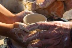 взрослая рука поданная baby& x27; руки s, который нужно работать с potter& x27; колесо s Стоковые Фотографии RF