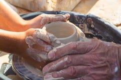 взрослая рука поданная baby& x27; руки s, который нужно работать с potter& x27; колесо s стоковые изображения rf