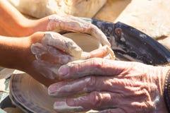 взрослая рука поданная baby& x27; руки s, который нужно работать с potter& x27; колесо s стоковое фото