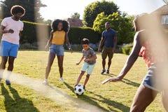 Взрослая семья играя футбол с молодым сыном в саде стоковые фотографии rf