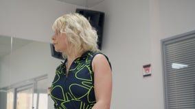 Взрослая тренировка женщины спорта протягивая тренировку пока подогрев в фитнес-клубе видеоматериал