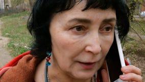 Взрослая элегантная женщина брюнета эмоционально говоря на ее смартфоне видеоматериал