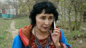 Взрослая элегантная женщина брюнета эмоционально говоря на ее смартфоне сток-видео