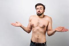 Взрослое положение без рубашки с смешиванием atrange различных эмоций на его стороне С его руками он показывает Стоковая Фотография
