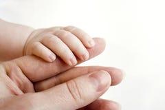 взрослое удерживание перста младенца Стоковые Изображения