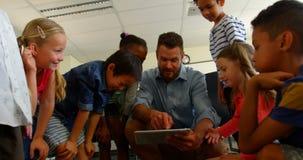 Взрослые кавказские дети школы мужского учителя уча на цифровом планшете в классе 4k сток-видео
