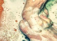 Взрослые любовники играя с ногой в ливне стоковые изображения