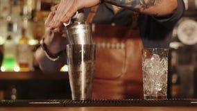 Взрослый бармен с татуировками на руках подготавливает коктеили, конец-вверх акции видеоматериалы