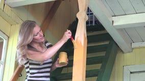 Взрослый женский работник крася новый деревянный поляка столбца с paintbrush в лестнице 4K сток-видео