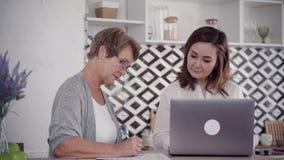 Взрослый и средн-достигшая возраста женщина дома используя tex ноутбука и сочинительства сток-видео