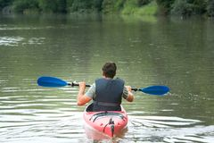 Взрослый мужчина в красном каное на озере горы стоковое фото rf