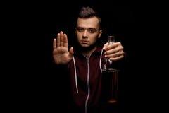 Взрослый мужчина в красном клобуке держа бутылку пива в его руке и показывая знак стопа на черной предпосылке стоковое фото rf