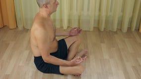 Взрослый облыселый человек сидя на поле, размышляющ в представлении йоги лотоса, концентрирующ в безмолвии, наблюдающ дыханием, о сток-видео