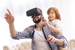 Взрослый отец использует стекла виртуальной реальности вместе с сыном дома стоковая фотография rf