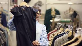Взрослый привлекательный искать женщины одежды в магазине одежды и смотреть черное платье но принимать его назад к другому акции видеоматериалы