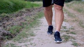 Взрослый спортсмен в голубых тапках и черных прогулках шортов на дороге акции видеоматериалы