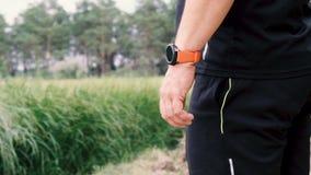 Взрослый спортсмен в черной форме стоит на его руке нося умные дозоры акции видеоматериалы