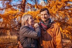 Взрослый сын и его средн-достигшая возраста мать имея потеху в парке осени Семейные ценности стоковая фотография rf