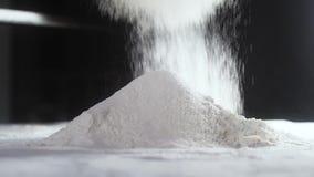 Взрослый хлебопек просеивает пшеничную муку Концепция подготовки теста для печь Мука летает белая пыль над деревянным столом Медл акции видеоматериалы