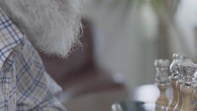 Взрослый человек играя шахматы сидя дома Бородатый человек думая который шахматная фигура для того чтобы сделать движение сток-видео