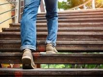 Взрослый человек идя вверх по деревянным лестницам Двигать вперед концепцию Стоковое фото RF