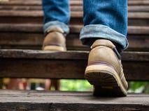 Взрослый человек идя вверх по деревянным лестницам Двигать вперед концепцию стоковые изображения rf