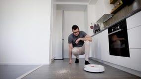 Взрослый человек кладет вокруг робототехнического пылесоса на пол кухни, переключает его дальше и идет вне акции видеоматериалы