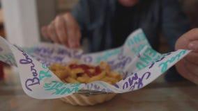 Взрослый человек льет французский картофель фри кетчуп, принимает одно и окунает, конец-вверх видеоматериал