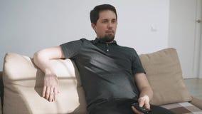 Взрослый человек расслабляющий перед ТВ, сидя в кресле и изменяя каналах видеоматериал