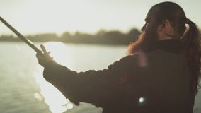 Взрослый человек с длинной бородой удит держащ рыболовную удочку Мужчина поднимает и понижает закручивать движение медленное сток-видео