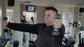 Взрослый человек с избыточным весом выполняет разводить с гантелями акции видеоматериалы