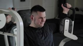 Взрослый человек с поездами избыточного веса его комод на имитаторе акции видеоматериалы