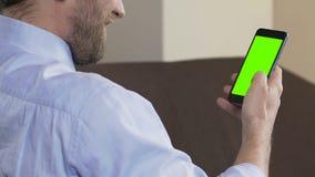 Взрослый человек с применением и усмехаться smartphone скроллинга бороды, зеленый экран сток-видео