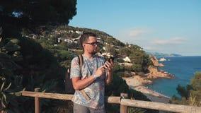 Взрослый townsman стоит в предпосылке береговой линии моря, используя смартфон видеоматериал