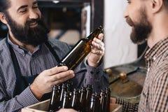 2 взрослых бородатых люд проверяют качество стекла пивной бутылки на винзаводе Процесс производства пива Стоковое Фото