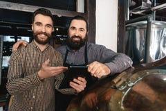 2 взрослых бородатых люд рассчитывать подачу воды таблетки для заваривать винзаводов Производить пива Стоковые Изображения