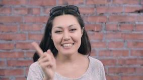 Взрослая девушка с черными длинными волосами радостно говорит в камере отливка Кирпичная стена видеоматериал