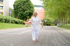 Взрослая женщина в весь белый идти на улицу стоковое фото rf