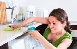 Взрослая женщина очищая вверх кухню Стоковая Фотография RF