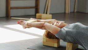 Взрослая женщина практикует йогу, используя оборудование - блок в руках сток-видео