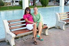 Взрослая женщина сидя на стенде в парке Стоковые Фотографии RF