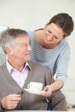 Взрослая дочь принося старшему отцу горячее питье дома стоковое изображение