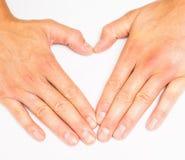 Взрослая персона создавая сердце с руками к серому цвету Стоковая Фотография