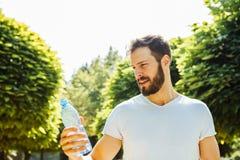 Взрослая питьевая вода человека от бутылки снаружи стоковое фото