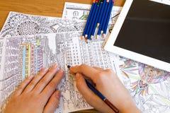 Взрослые книги расцветки с карандашами, новой тенденцией сбрасывать стресса, персоной концепции mindfulness крася иллюстративной Стоковые Изображения
