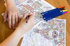 Взрослые книги расцветки с карандашами, новой тенденцией сбрасывать стресса, персоной концепции mindfulness крася иллюстративной Стоковое Изображение RF