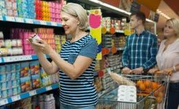 Взрослые семьи из трех человек выбирая югурт в магазине Стоковая Фотография RF