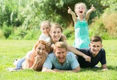 Взрослые человек и женщина при 4 дет лежа в парке Стоковое Изображение