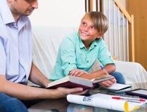 Взрослые человек и мальчик с компьтер-книжкой внутри помещения Стоковое Фото